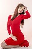 La chica joven con una figura hermosa en un vestido rojo de moda en miniskirt ceñido y los tacones altos y plataforma rojos se vi Foto de archivo libre de regalías