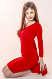 La chica joven con una figura hermosa en un vestido rojo de moda en miniskirt ceñido y los tacones altos y plataforma rojos se vi Imagen de archivo libre de regalías