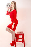 La chica joven con una figura hermosa en un vestido rojo de moda en miniskirt ceñido y los tacones altos y plataforma rojos se vi Fotografía de archivo