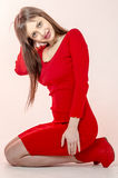 La chica joven con una figura hermosa en un vestido rojo de moda en miniskirt ceñido y los tacones altos y plataforma rojos se vi Imagen de archivo
