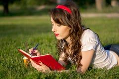 La chica joven con una libreta y la pluma en un verano parquean Imagen de archivo libre de regalías