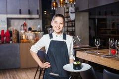 La chica joven con una sonrisa hermosa un camarero sostiene en sus manos un plato dulce del postre de la orden de la cocina itali foto de archivo libre de regalías
