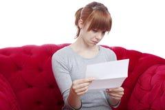 La chica joven consigue malas noticias en el sofá rojo Fotografía de archivo libre de regalías