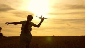 La chica joven corre con un avión del juguete en el campo en los rayos del slint los ni?os juegan el aeroplano del juguete sueños metrajes