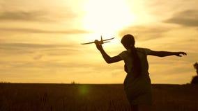 La chica joven corre con un avión del juguete en el campo en los rayos del slint los ni?os juegan el aeroplano del juguete Sueños almacen de metraje de vídeo