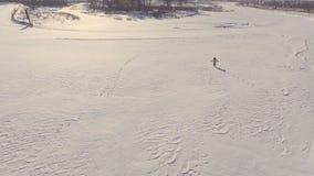 La chica joven corre a través del espacio abierto en el invierno, visión aérea almacen de metraje de vídeo