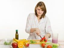 La chica joven corta la ensalada del vegetariano de la pimienta Foto de archivo libre de regalías
