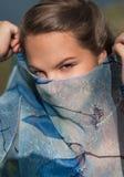 La chica joven cubrió su cara con una bufanda azul Fotos de archivo