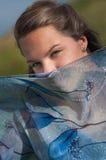 La chica joven cubrió su cara con una bufanda azul Imagenes de archivo