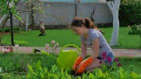 La chica joven cuida para el césped cerca de la casa almacen de video
