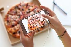 La chica joven da tomar una imagen de su comida - una caja de pizza foto de archivo libre de regalías
