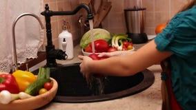 La chica joven da verduras que se lavan en el fregadero de cocina metrajes