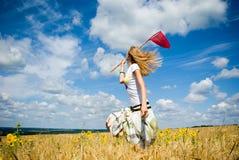 La chica joven de cabeza blanca coge mariposas Imagenes de archivo