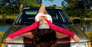 La chica joven de la belleza pone en el coche en la puesta del sol del verano Foto de archivo libre de regalías