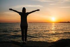 La chica joven de la parte posterior aumentó sus manos para arriba contra el fondo de la puesta del sol al lado del mar Libertad, Foto de archivo