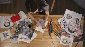 La chica joven de la visión superior dibuja con los lápices almacen de video