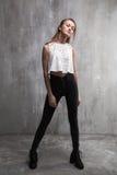 La chica joven de moda que se colocaba en un fondo gris texturizó wa Imagenes de archivo