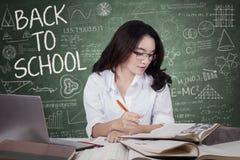 La chica joven de nuevo a escuela y aprende en clase Fotografía de archivo libre de regalías