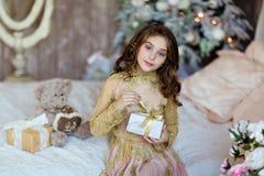 La chica joven de pelo largo encantadora con los ojos azules abre el regalo encendido Fotografía de archivo libre de regalías