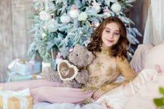 La chica joven de pelo largo hermosa que sostiene un oso de peluche sonríe encendido Fotos de archivo libres de regalías