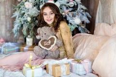 La chica joven de pelo largo hermosa que sostiene un oso de peluche sonríe encendido Fotografía de archivo libre de regalías