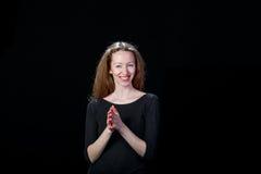 La chica joven de risa con el pelo marrón frota sus palmas contra un fondo negro Imagen de archivo libre de regalías