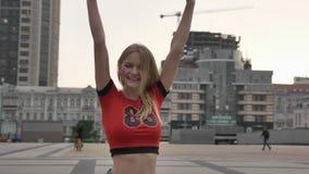 La chica joven de un fanático del fútbol rubio de Inglaterra, disfruta, aumenta sus brazos para arriba, disfruta en fps de la vic metrajes