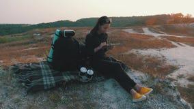 La chica joven del inconformista con la mochila en el top de una roca disfruta del propósito de la puesta del sol y de usar la ta almacen de video
