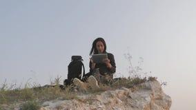 La chica joven del inconformista con la mochila en el top de una roca disfruta del propósito de la puesta del sol y de usar la ta metrajes