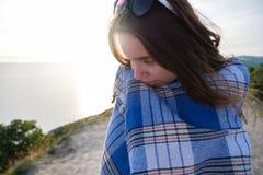 La chica joven del primer se sienta en una montaña, envuelta en una manta Tarde fresca del verano en las montañas Imagenes de archivo