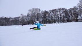 La chica joven desliza abajo la diapositiva en nieve en un tubo inflable de la nieve y agita su mano Muchacha feliz que juega en  almacen de video