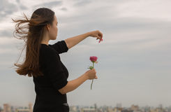 La chica joven despluma un pétalo de una rosa sobre una opinión de la ciudad Fotografía de archivo