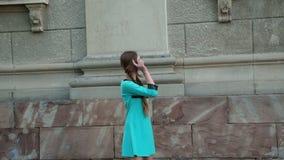 La chica joven despreocupada presenta con sonrisa en la construcción al aire libre 4K metrajes