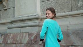 La chica joven despreocupada presenta con sonrisa en la construcción al aire libre 4K almacen de video