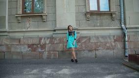 La chica joven despreocupada presenta con sonrisa en la construcción al aire libre 4K almacen de metraje de vídeo