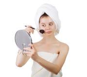 La chica joven después de una ducha en toallas con un espejo y un cepillo para un maquillaje Fotos de archivo libres de regalías