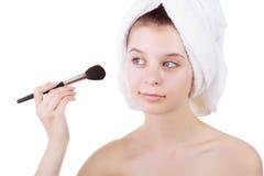 La chica joven después de una ducha en toallas y con el cepillo para un maquillaje Imagen de archivo libre de regalías