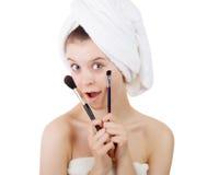 La chica joven después de una ducha en toallas y con los cepillos para un maquillaje Imagenes de archivo