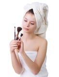 La chica joven después de una ducha en toallas y con los cepillos para un maquillaje Fotos de archivo