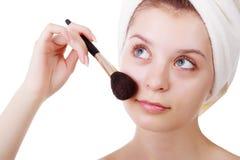 La chica joven después de una ducha en toallas y con los cepillos para un maquillaje foto de archivo