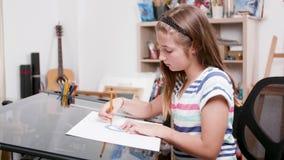 La chica joven dibuja algunas líneas usando un lápiz y un prolongador metrajes