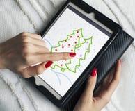 La chica joven dibuja el árbol de navidad en la tableta Imagenes de archivo