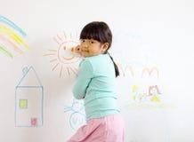 La chica joven dibuja en la pared imagen de archivo