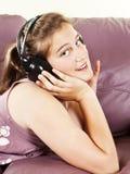 La chica joven disfruta de música que escucha en auriculares Imagenes de archivo