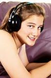 La chica joven disfruta de música que escucha en auriculares Imagen de archivo