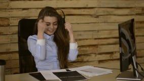 La chica joven disfruta de su trabajo en la oficina delante del ordenador con la pantalla táctil Agente del centro de llamada metrajes