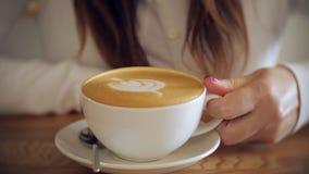 La chica joven disfruta del aroma del café delicioso almacen de metraje de vídeo