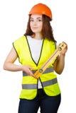 La chica joven el constructor en un casco y un chaleco con el nivel en manos Fotos de archivo