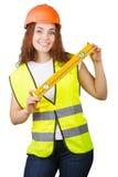 La chica joven el constructor en un casco y un chaleco con el nivel en manos Imagenes de archivo