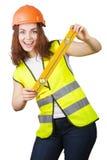La chica joven el constructor en un casco y un chaleco con el nivel en manos Imagen de archivo libre de regalías